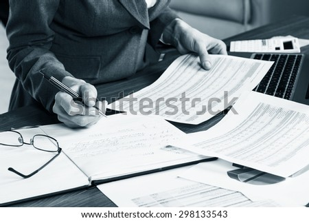 Close up of a female hand calculating, on the office desk. - stock photo