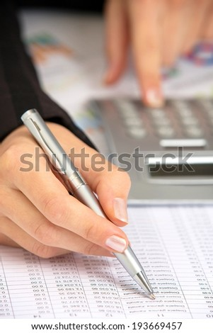 Close up of a female hand calculating, over documents. - stock photo