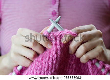 Close up of a female hands knitting pink woolen threads - stock photo
