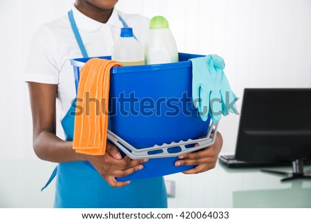 Close-up Of A Female Janitor Holding Cleaning Equipments - stock photo