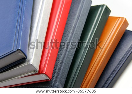 Close-up of a few colored books (notebooks, diaries). - stock photo
