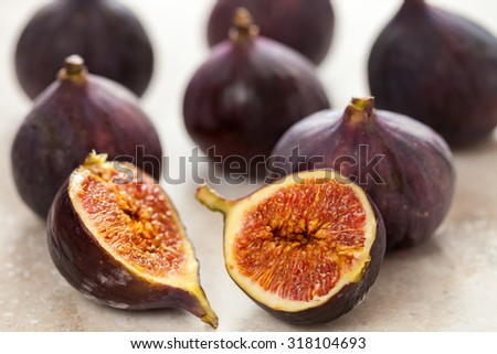 Close-up of a fig sliced in half on a ceramic tile surface. several whole figs in the background out of focus. - stock photo