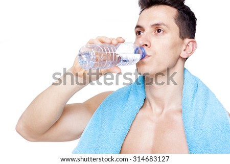 Close-up of a fit man drinking a bottle of water, isolated on white background - stock photo