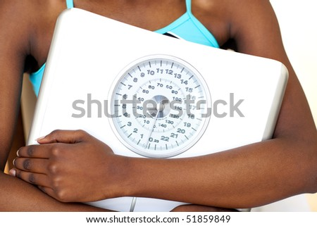 Close-up of a fitness woman with thumb up holding a weight scale against a white background - stock photo