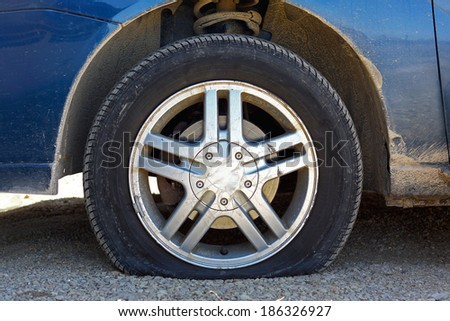 close up of a flat tire of a rusty old blue car centered on gravel road - stock photo