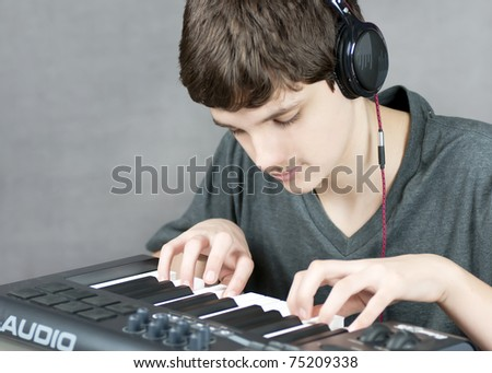 Close-up of a focused teen playing his keyboard. - stock photo