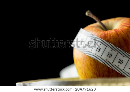 Close-up of a fresh tasty apple, natural source of vitamins and minerals, wrapped with a white measuring tape, with copy space on black, concept of dieting and healthy nutritious food. - stock photo
