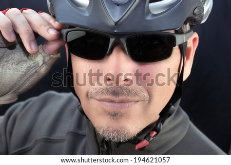 Close-up of a friendly bicycle courier putting on his sunglasses. - stock photo