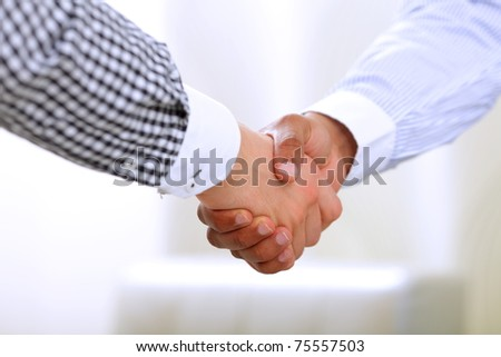 Close-up of a friendly handshake between african american and caucasian american business men - stock photo