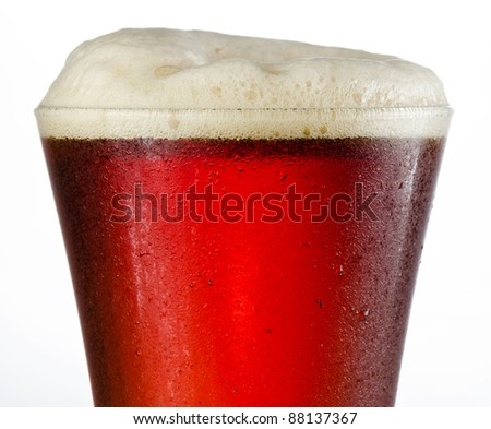 Close up of a full to rim cold beer in pilsner style glass with head above rim - stock photo
