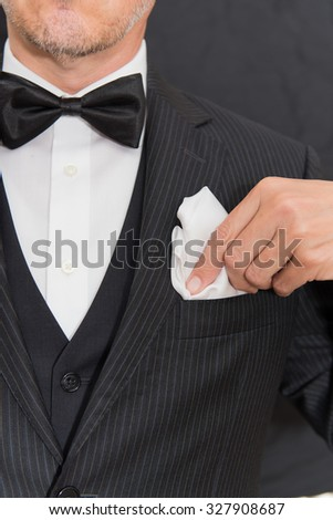 Close-up of a gentleman wearing Black Tie fixes his pocket square, vertical. - stock photo