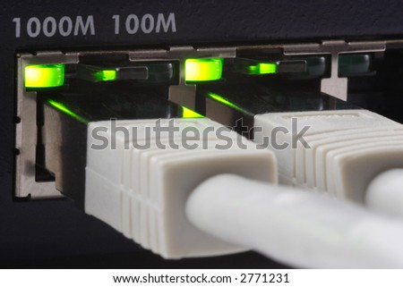 Close-up of a gigabit switch and two plugged cat6 network cables - stock photo