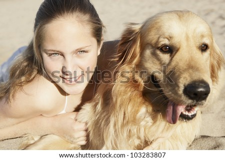 Close up of a girl and her dog on the beach. - stock photo