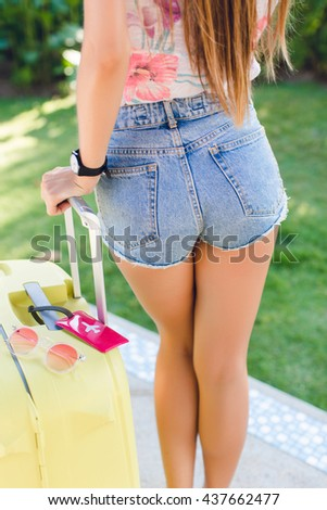 Close-up of a girl's back. Girl wears denim shorts, bright t-shirt and black watch. She stands next to yellow suitcase. She has slim tanned legs. There is a red label on suitcase with white plane. - stock photo