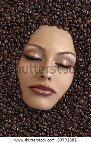close up of a girl's face immersed in coffee beans keeping her eyes closed - stock photo