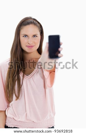 Close-up of a girl showing a smartphone against white background - stock photo