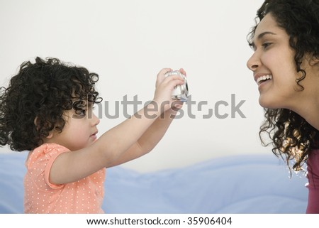 Close-up of a girl taking a picture of her mother with a digital camera - stock photo