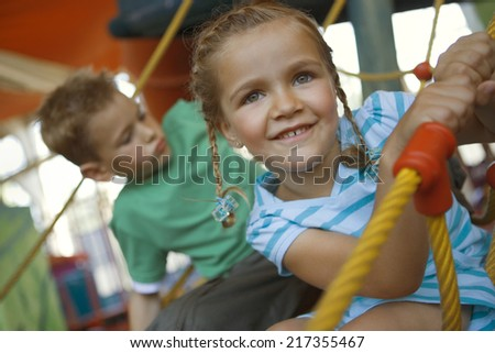 Close-up of a girl with a boy on a rope climbing net - stock photo