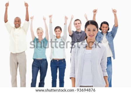 Close-up of a girl with people raising their arms with their thumbs up in background - stock photo
