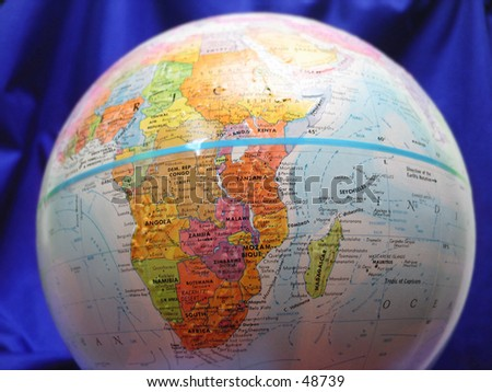 Close up of a globe, Blue material in background. - stock photo