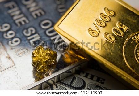 Close-up of a gold-ingot and nugget on top of a troy ounce silver and dollar banknotes - stock photo