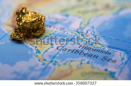 Close-up of a gold nugget on top of a map of Mexico - stock photo