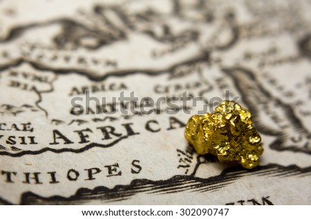 Close-up of a gold nugget on top of an old map of Africa - stock photo