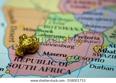 Close-up of a gold nugget on top of an old map of South Africa - stock photo