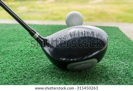 Close-up of a golf ball and a golf wood on a driving range - stock photo