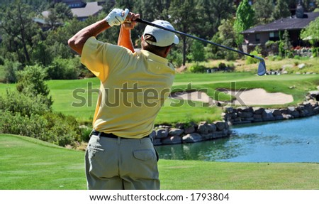 Close-up of a golfer hitting over water - stock photo