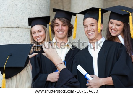 Close-up of a graduate taking a picture of her smiling friend in front of the university - stock photo