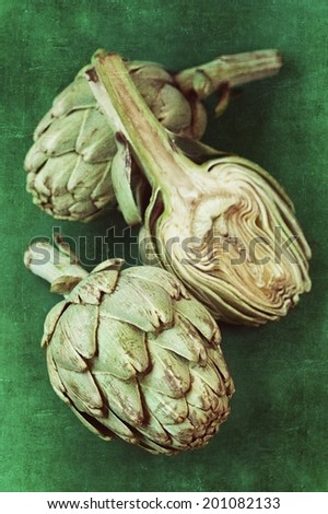 close up of a green fresh artichoke on a green background with old paper texture . - stock photo