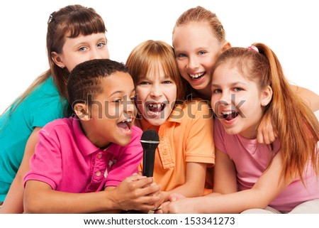 Close-up of a group of happy exited diversity looking kids, boys and girls, singing together sitting on the coach in living room - stock photo
