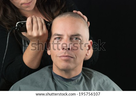 Close-up of a hair stylist using clippers to shave her Clients head. - stock photo