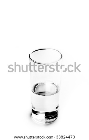 Close-up of a half empty glass of water on a white background - stock photo