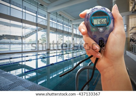 Close up of a hand holding a chronometer outside of the swimming pool - stock photo