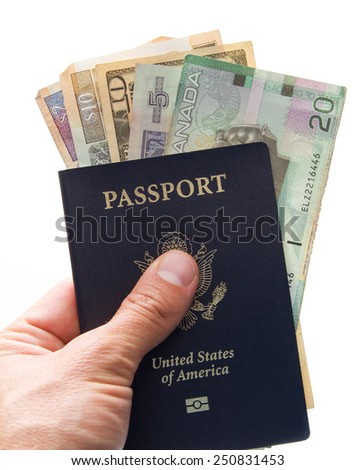close up of a hand holding an american passport with money form different countries inside of it - stock photo