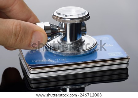 Close-up Of A Hand Holding Medical Stethoscope On Credit Card Stack - stock photo