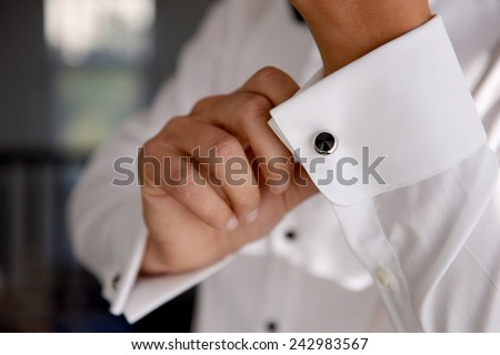close up of a hand man how wears white shirt and cufflink - stock photo