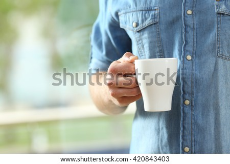 Close up of a hand of man holding a coffee cup beside a window with a green background outside - stock photo