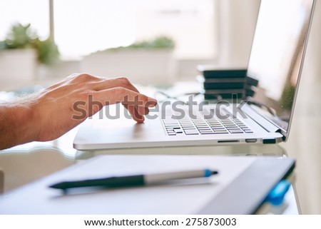 close up of a hand scrolling on a notebook, with copy space and a digital tablet in the foreground and hard drives in the background - stock photo