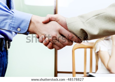 Close-up of a handshake of two businesspeople at the office. - stock photo