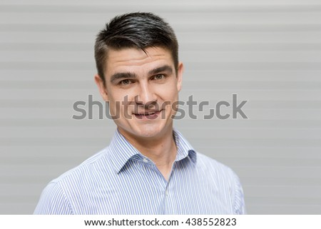 Close up of a handsome young man in a shirt, smilimg, looking at camera, opposite a grey wall in the background - stock photo