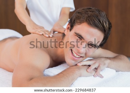 Close up of a handsome young man receiving shoulder massage at spa center - stock photo