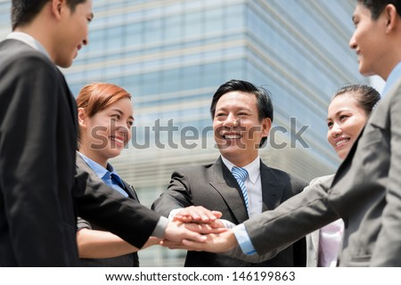 Close-up of a happy business team posing in front of the modern building - stock photo