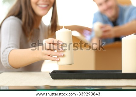Close up of a happy couple hands unpacking a box when moving home and placing objects - stock photo