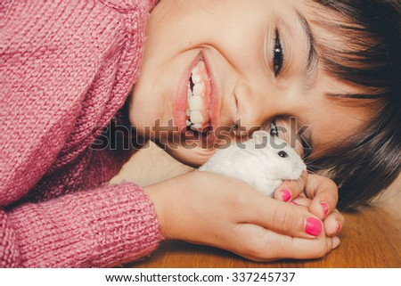 Close up of a happy girl hugging her hamster lovingly - stock photo