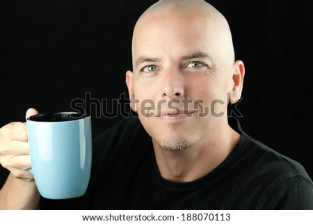 Close-up of a happy, peaceful bald man lifting his mug to camera. - stock photo