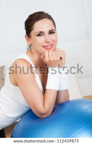 Close up of a happy smiling woman with a large blue pilates ball in a health and fitness concept - stock photo