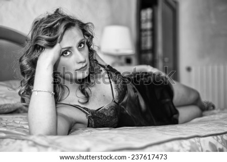 Close up of a happy young woman looking at something interesting while lying on the bed. - stock photo